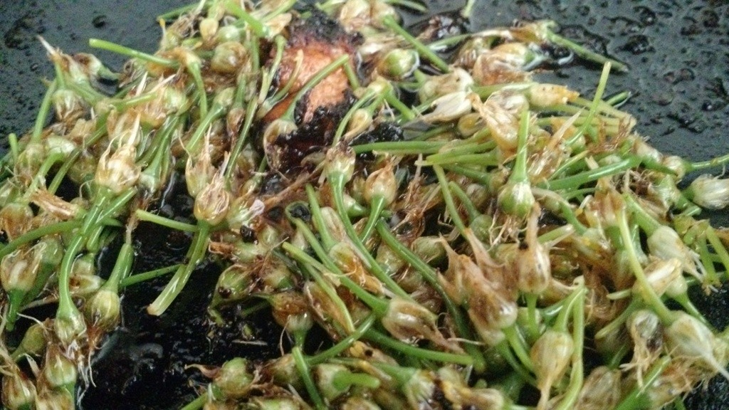 scallion blossoms cooking in skillet